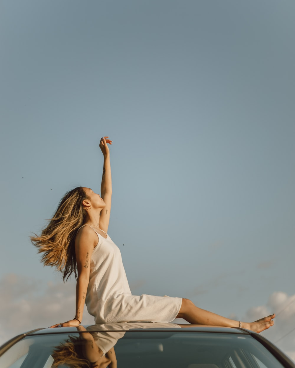 woman in white sleeveless dress raising her right hand