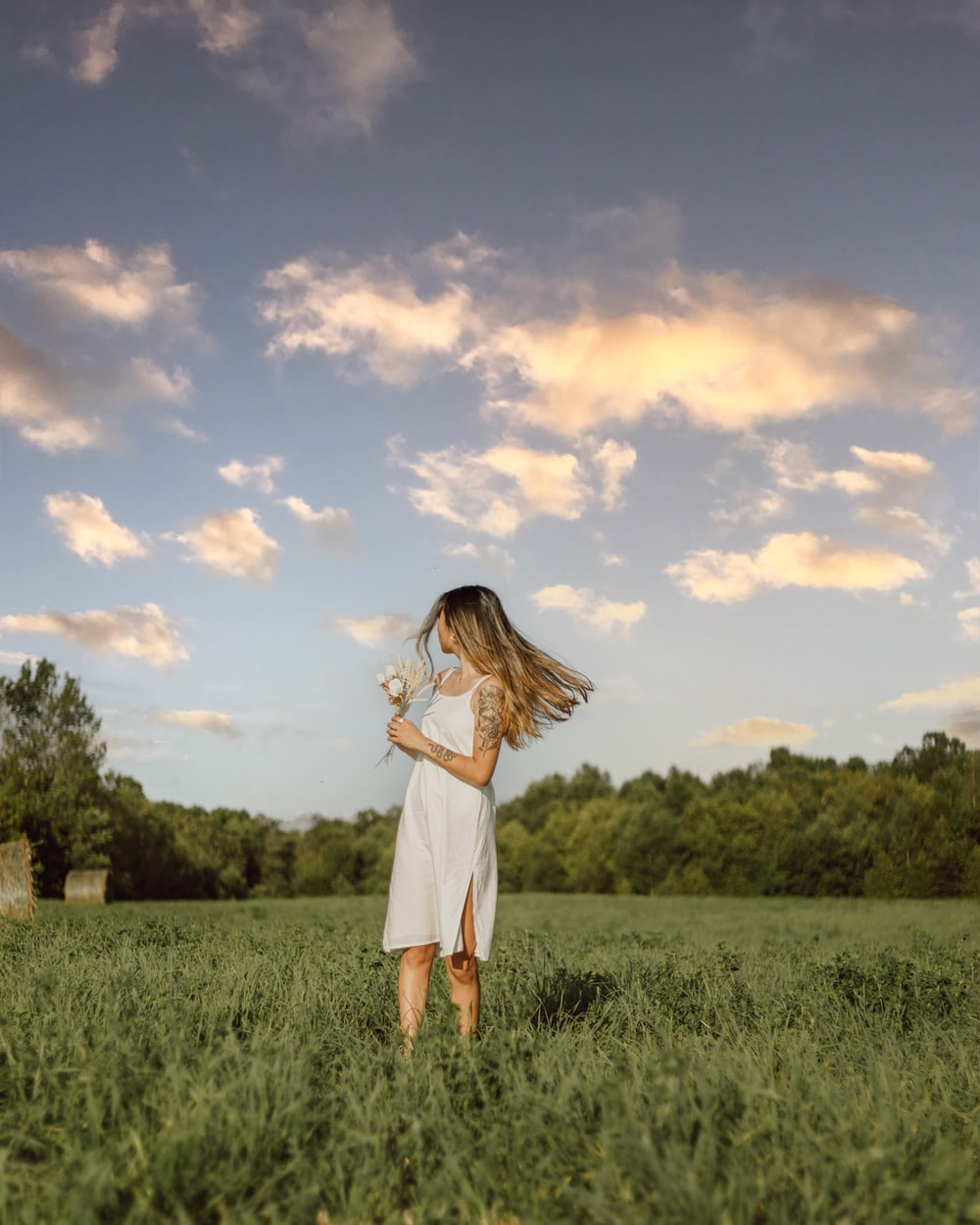 woman in white dress standing on green grass field under blue and white cloudy sky during
