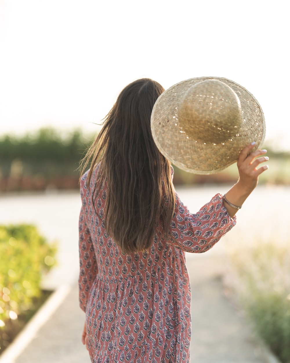 woman in red and blue long sleeve shirt holding white ball during daytime