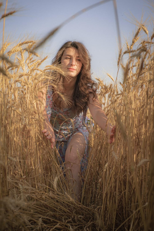 woman in blue denim shorts sitting on brown grass during daytime