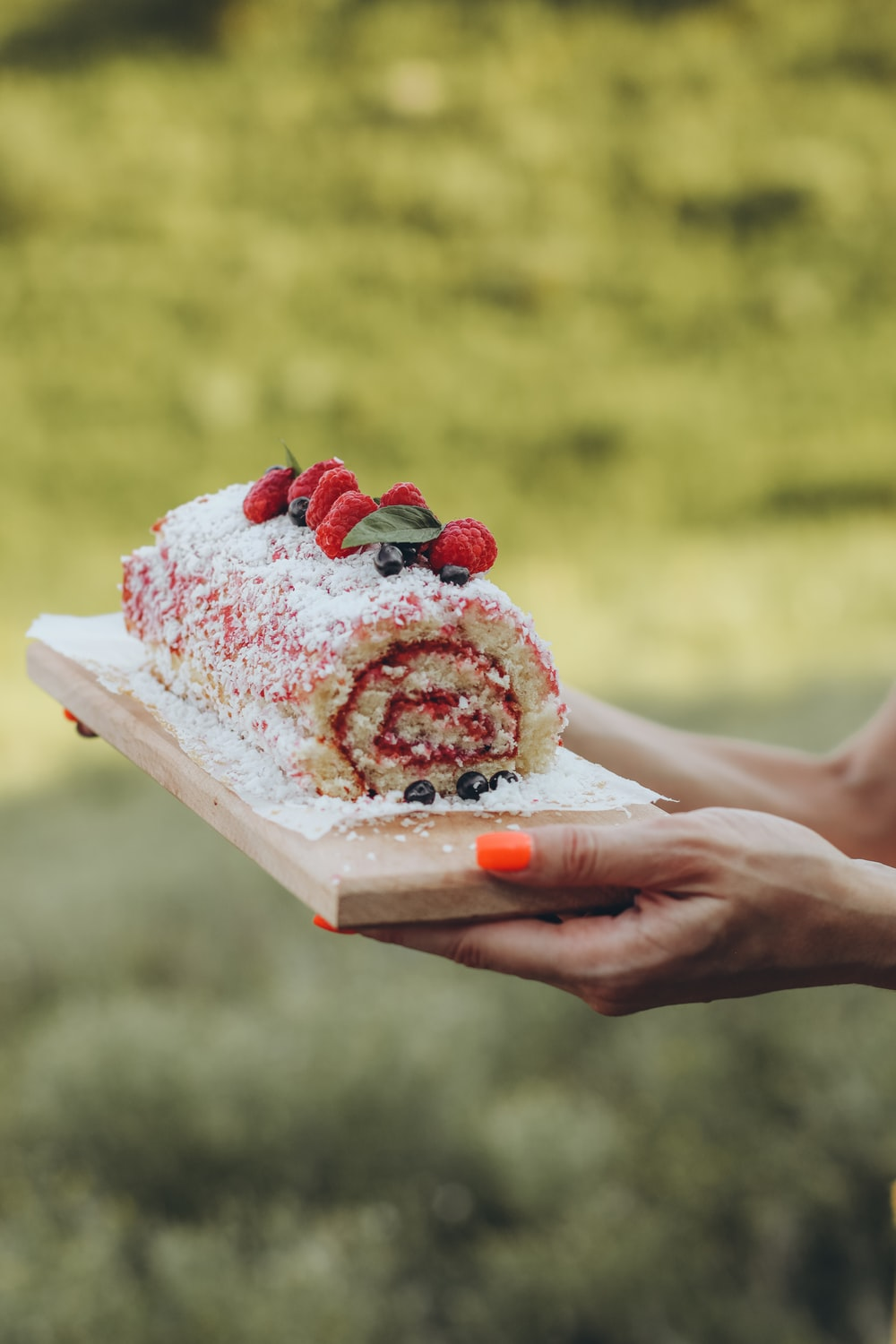 person holding white and red cake