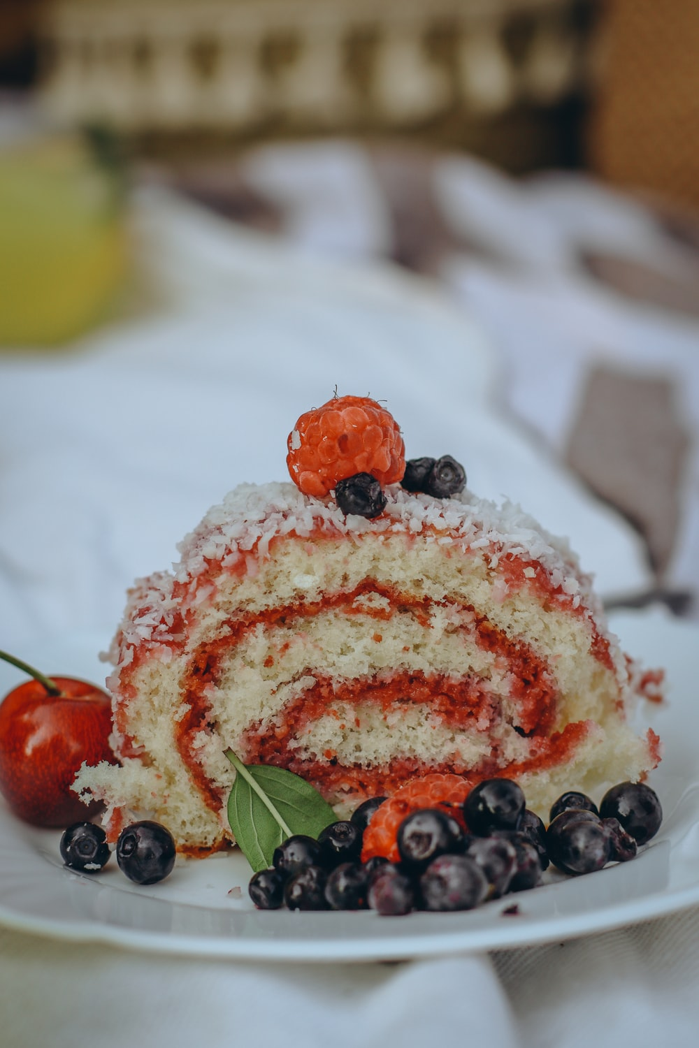white and red cake with fruits on top