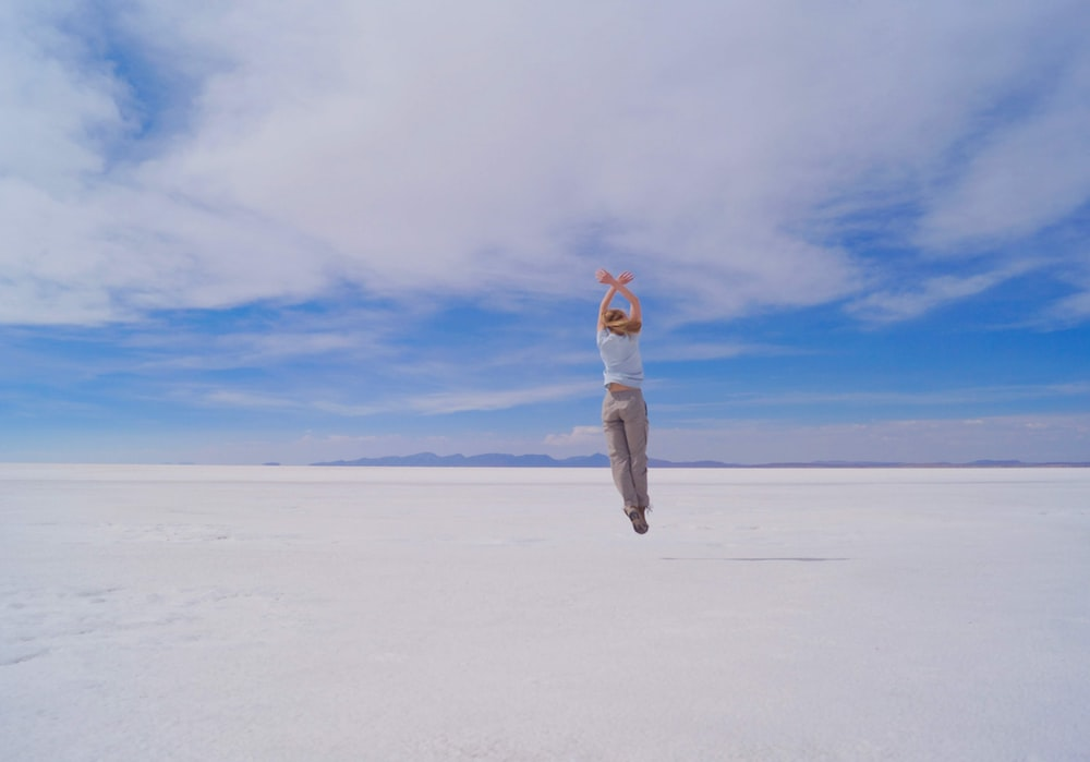 woman in white jacket and gray pants standing on white sand under blue sky during daytime