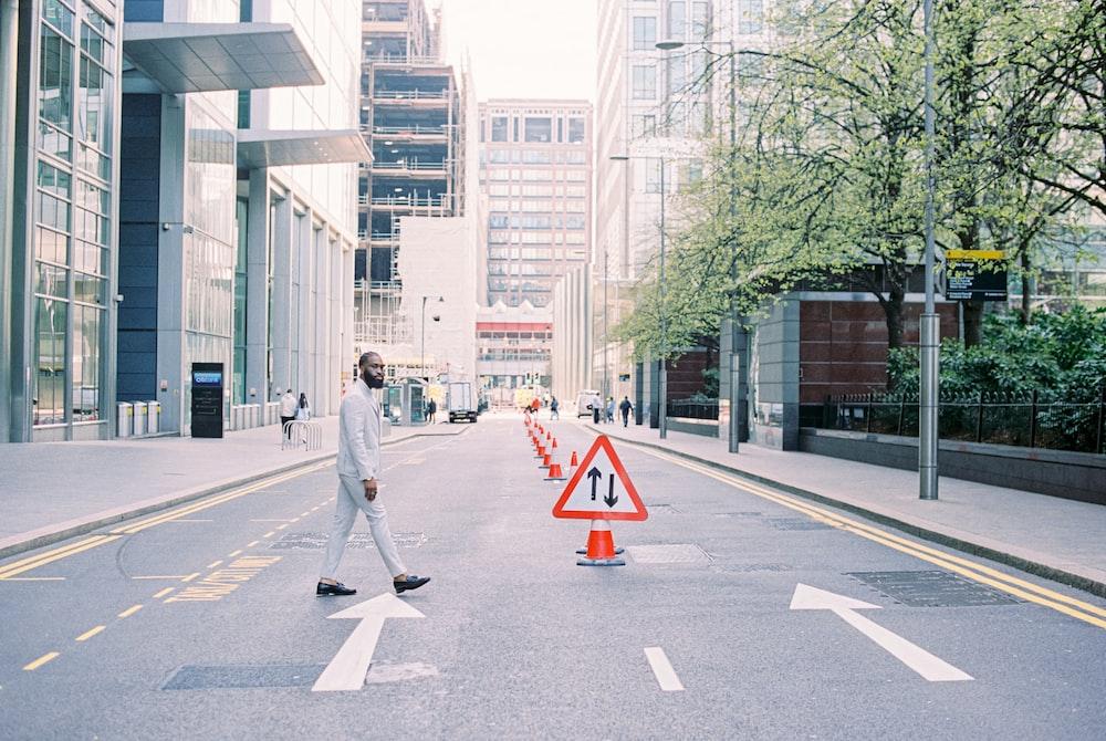 man in gray jacket and gray pants walking on pedestrian lane during daytime