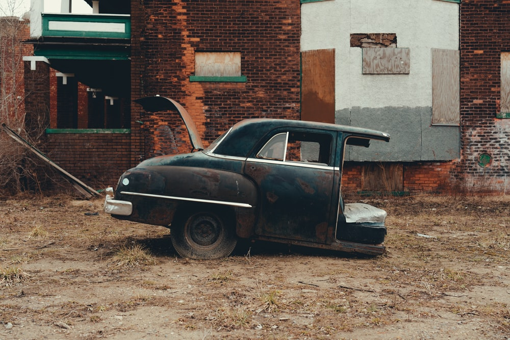 black classic car parked beside brown brick building