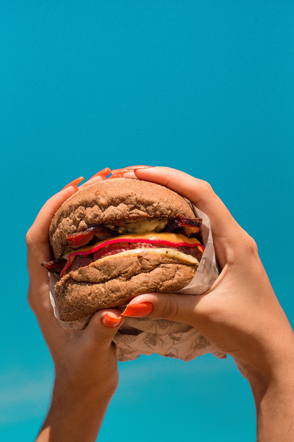person holding burger with patty and lettuce