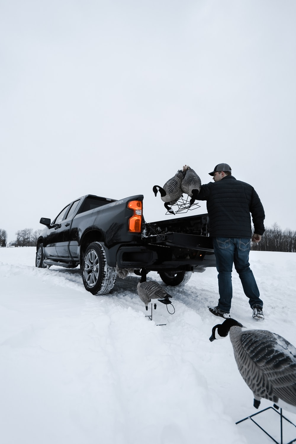 man in black jacket and blue denim jeans standing beside black suv on snow covered ground