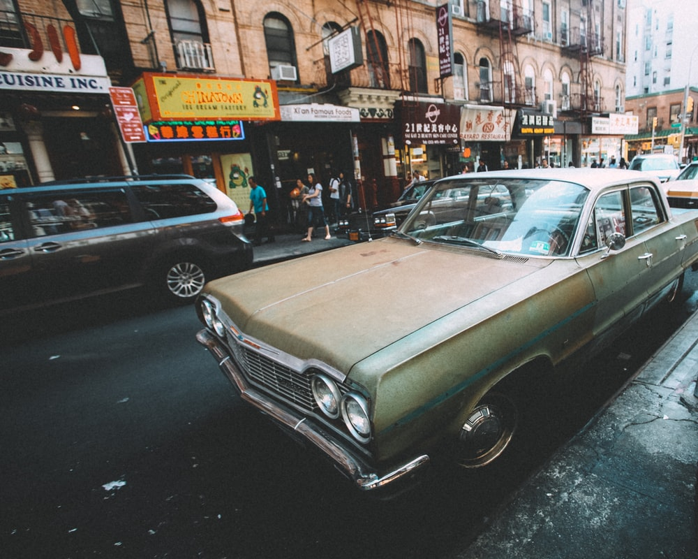 green classic car parked on sidewalk during daytime