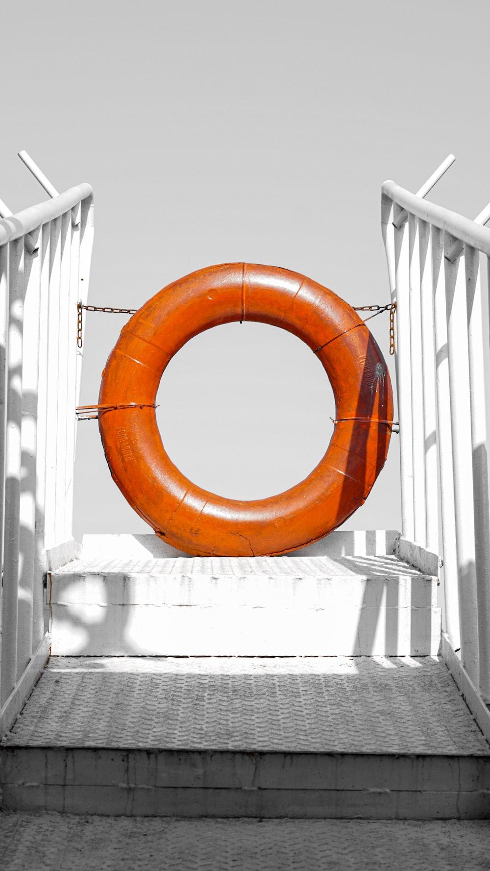 orange life buoy on white wooden fence