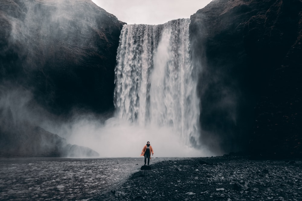 woman in red jacket standing near waterfalls during daytime