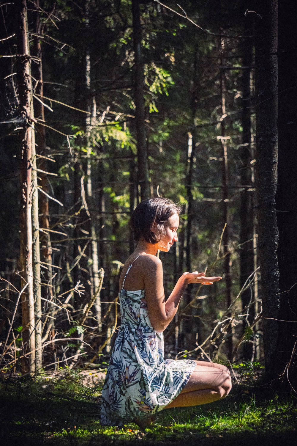 woman in blue and white floral spaghetti strap dress standing in forest during daytime