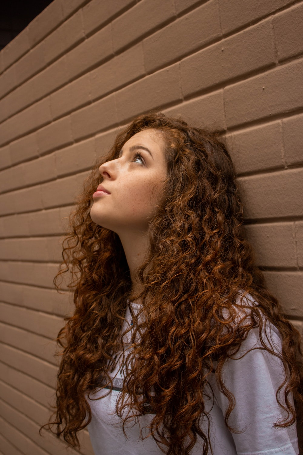 woman in white shirt standing beside brown wall