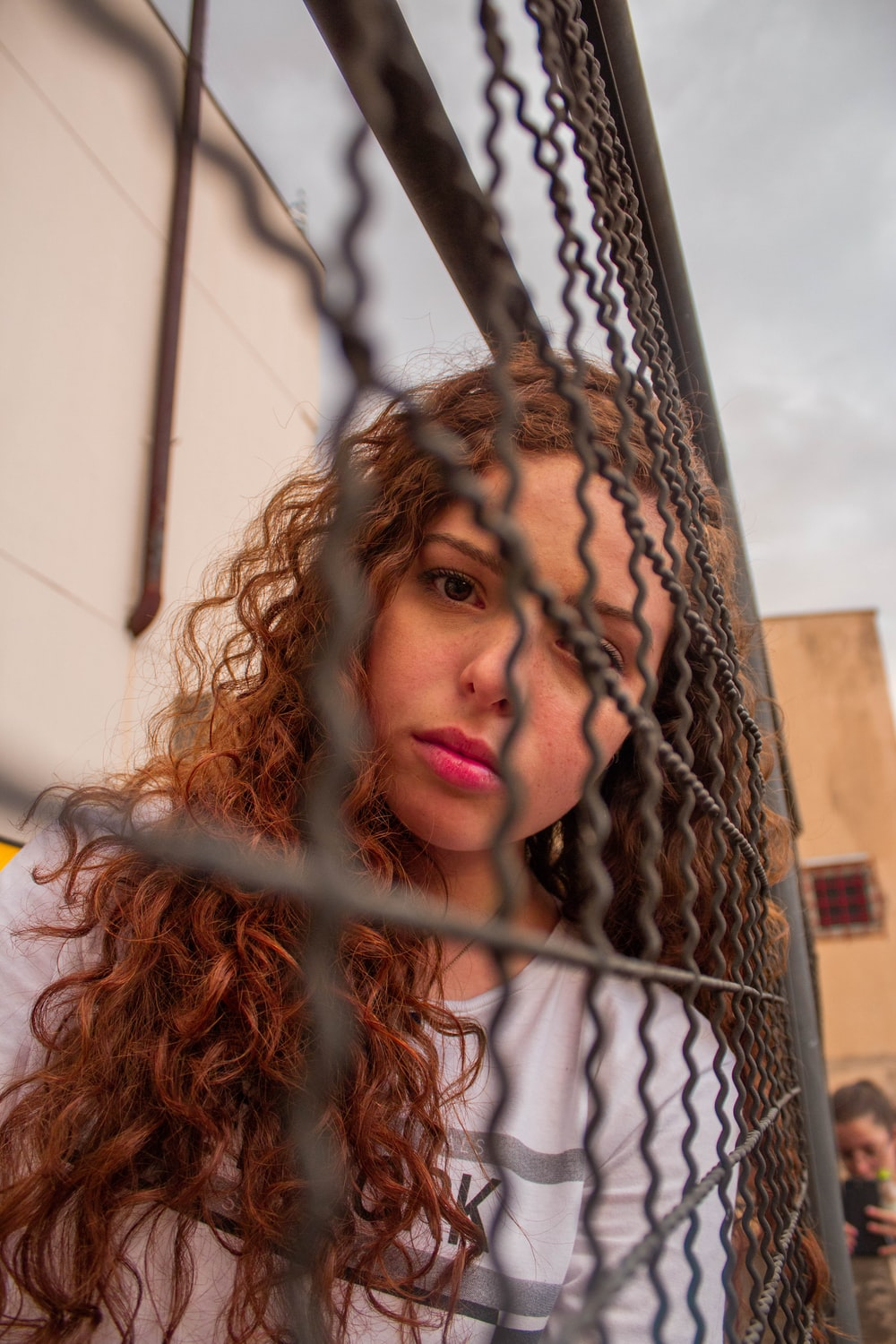 woman in white shirt leaning on brown metal fence during daytime