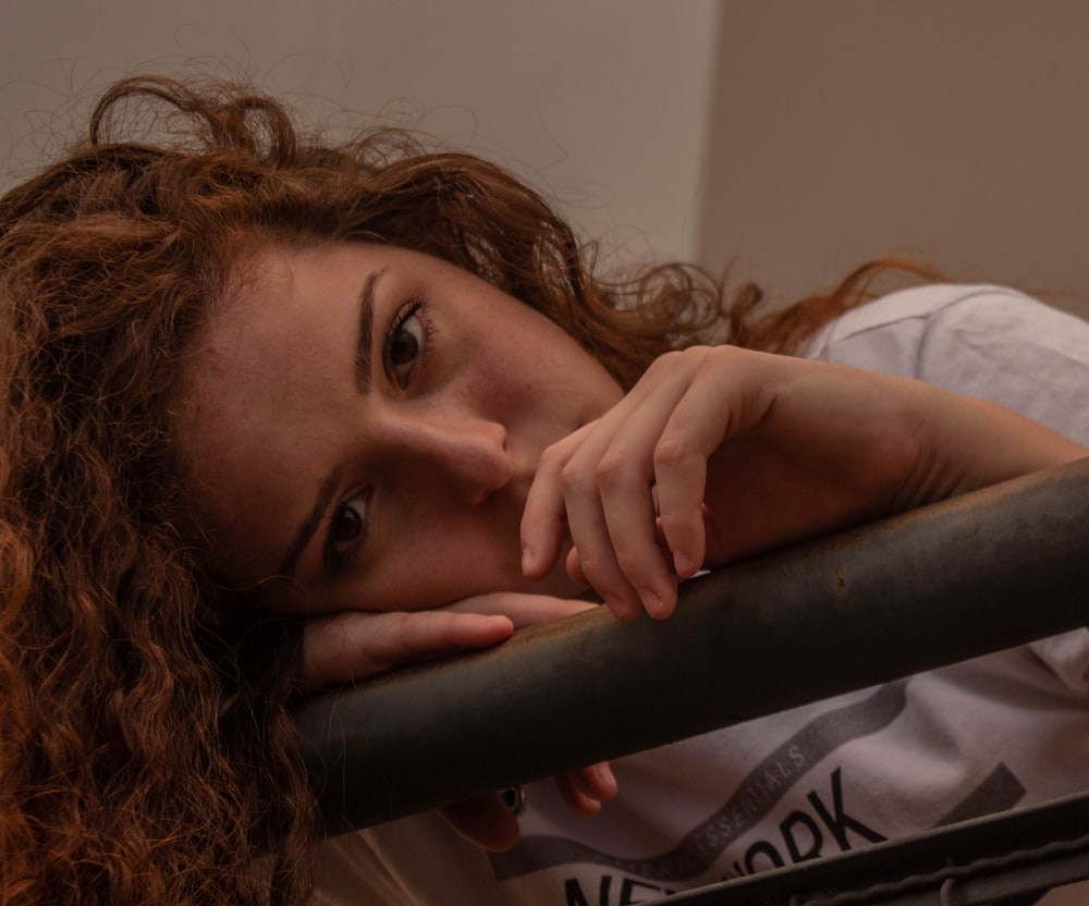 girl in white shirt lying on bed