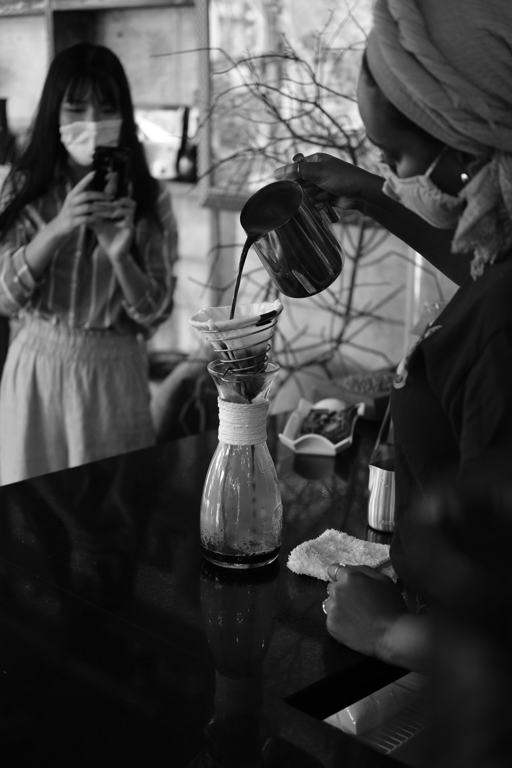 grayscale photo of woman pouring water on clear glass bottle