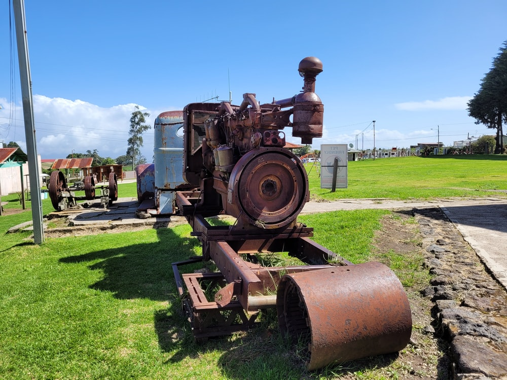 brown and black tractor on green grass field during daytime
