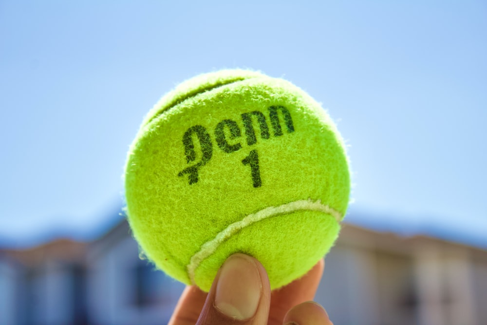 green tennis ball on hand