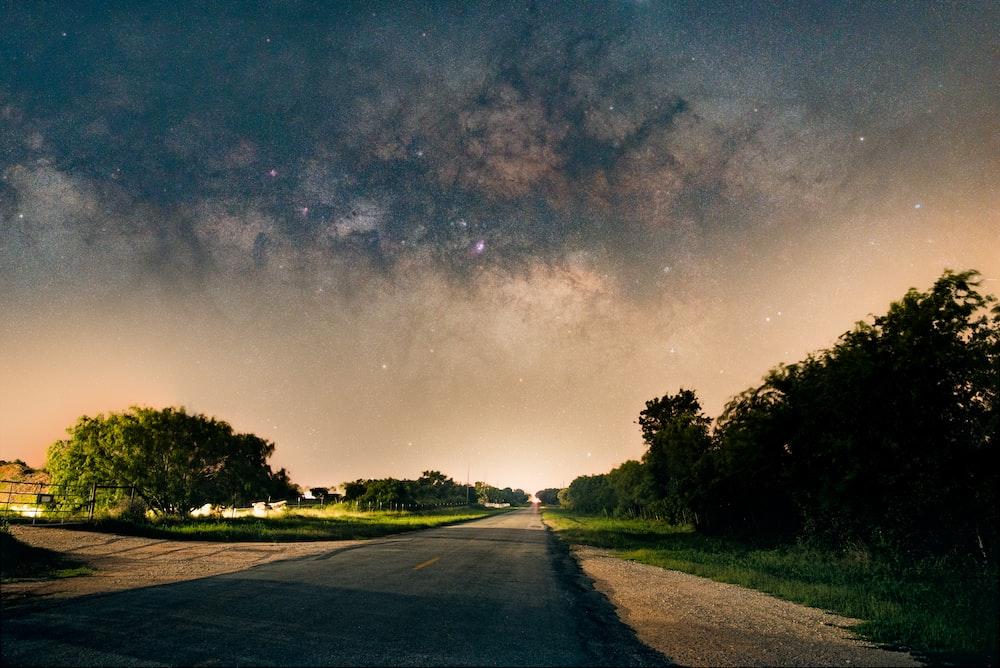 gray asphalt road between green trees under blue sky during night time