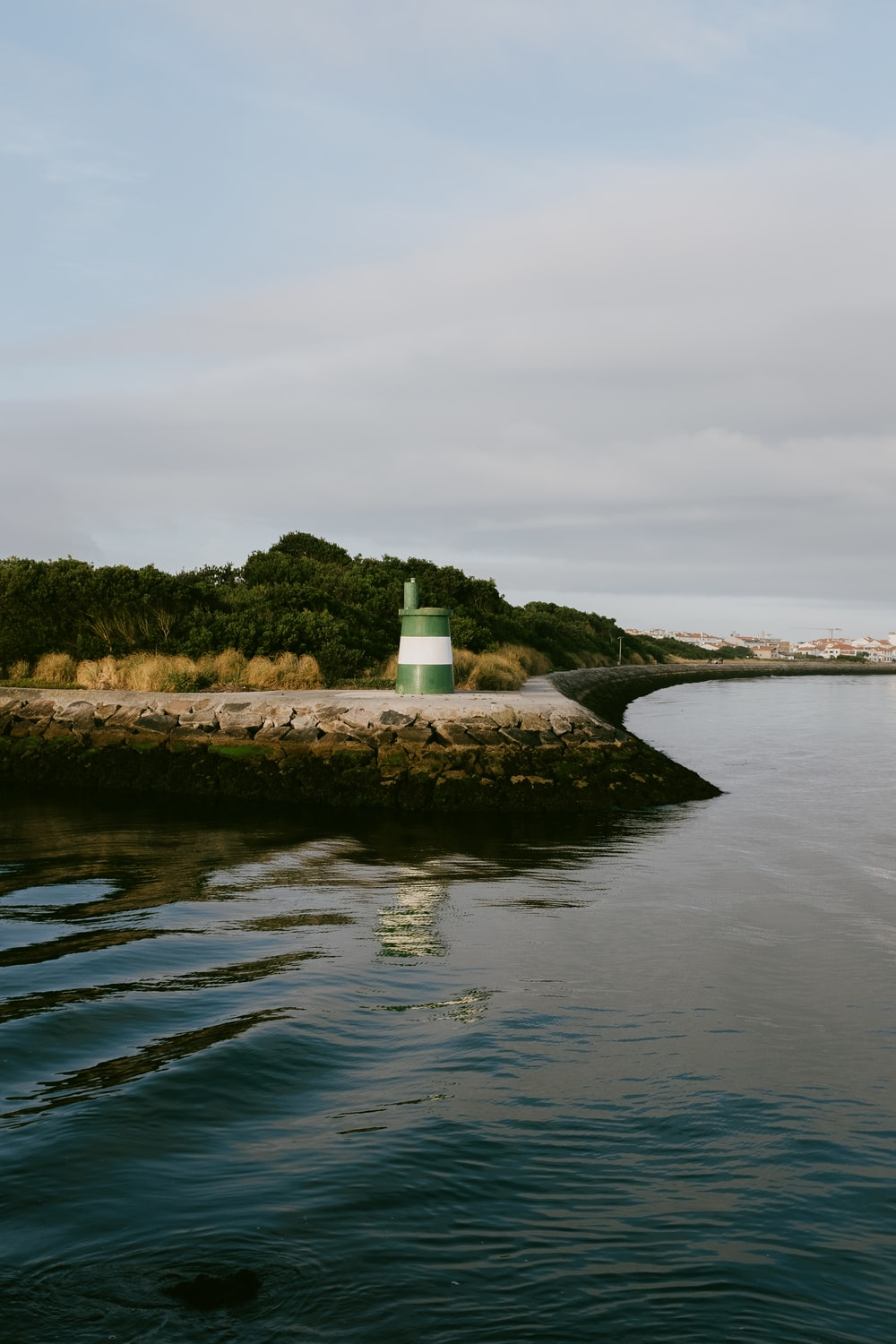 white lighthouse near body of water during daytime