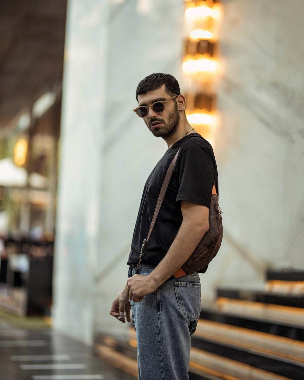 man in black crew neck t-shirt and blue denim jeans wearing black sunglasses
