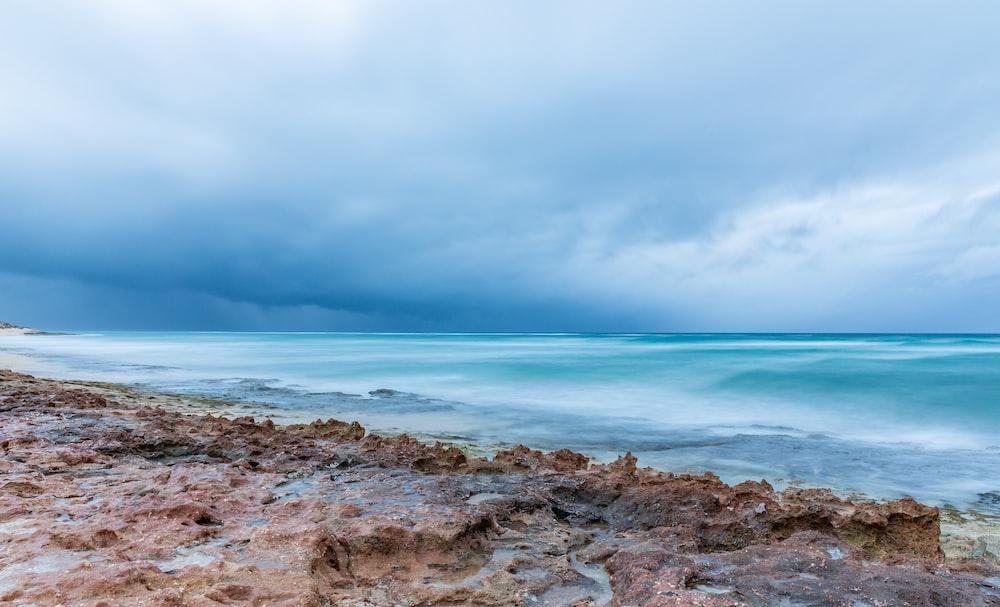 brown rocky shore under gray cloudy sky