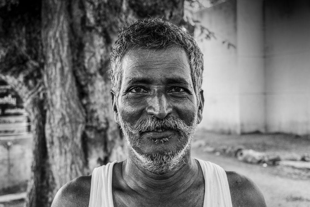 man in tank top in grayscale photography