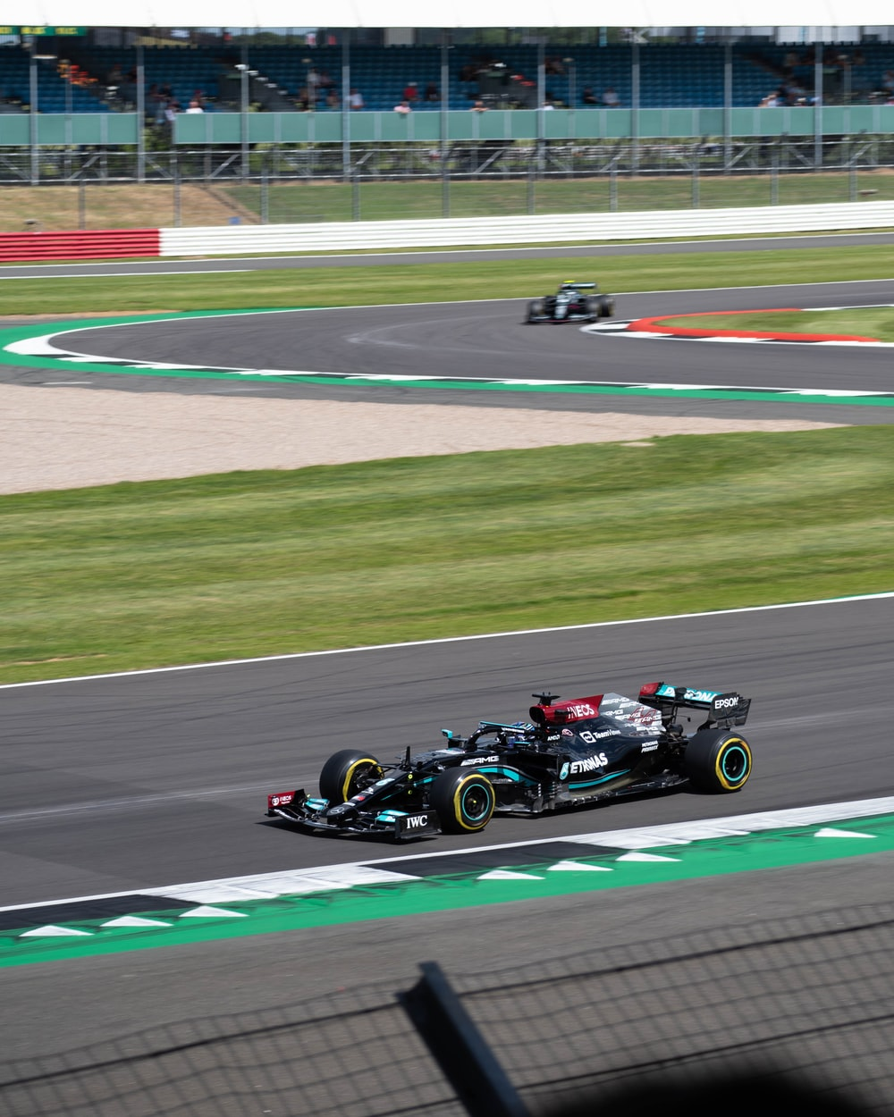 black and red f 1 car on track field during daytime