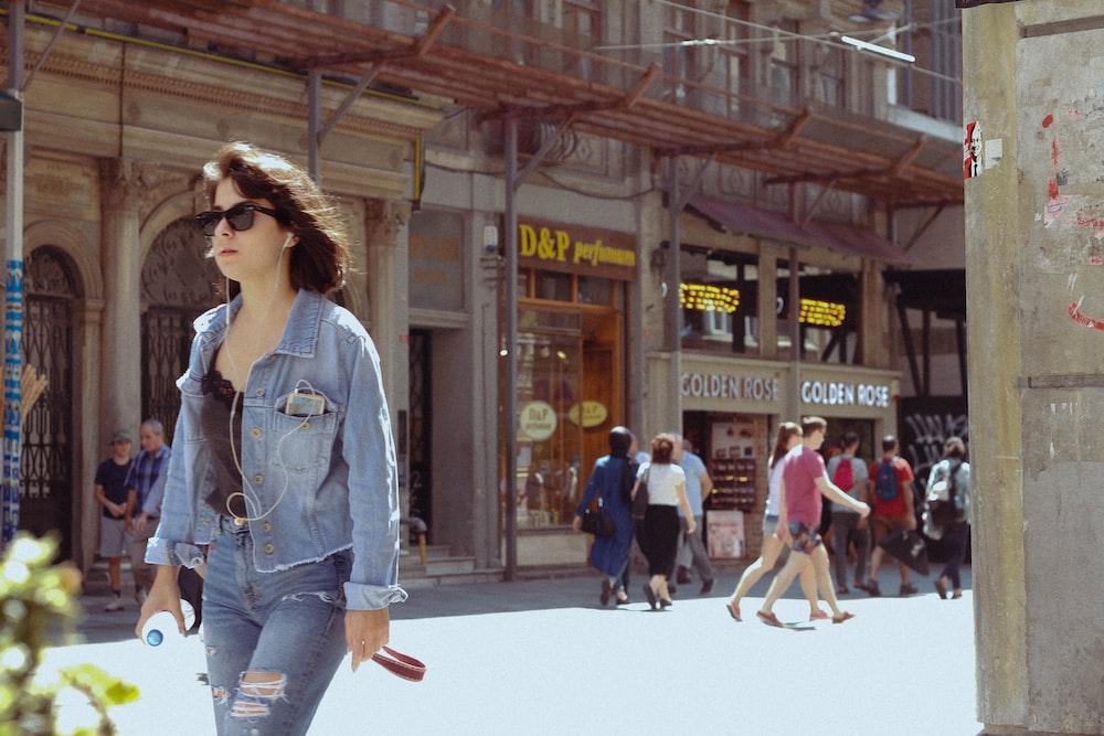 woman in blue denim jacket and blue denim jeans walking on street during daytime