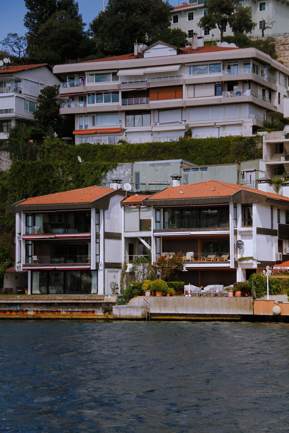 white and brown concrete house beside body of water during daytime