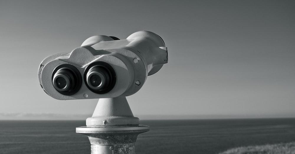 gray binoculars on green textile