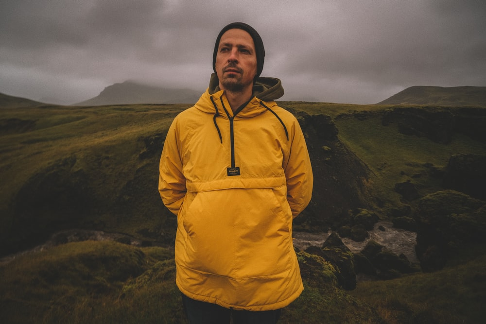man in green zip up jacket standing on hill during daytime