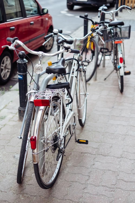 red city bike parked on sidewalk during daytime