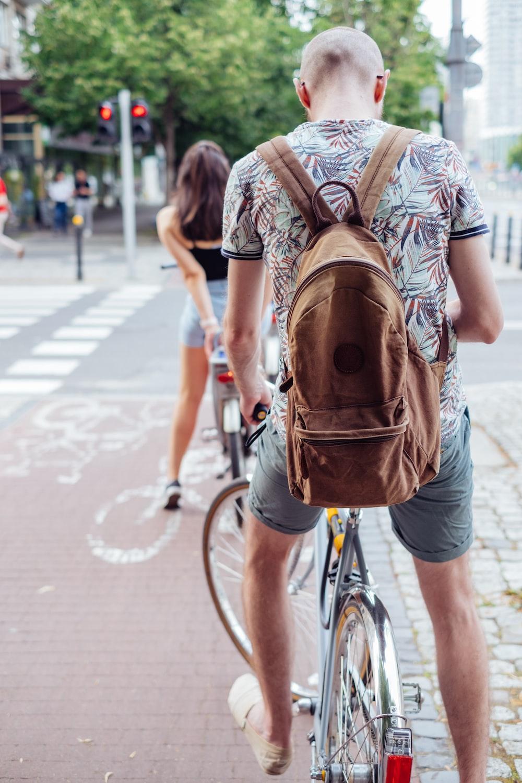 man in brown t-shirt riding bicycle on road during daytime