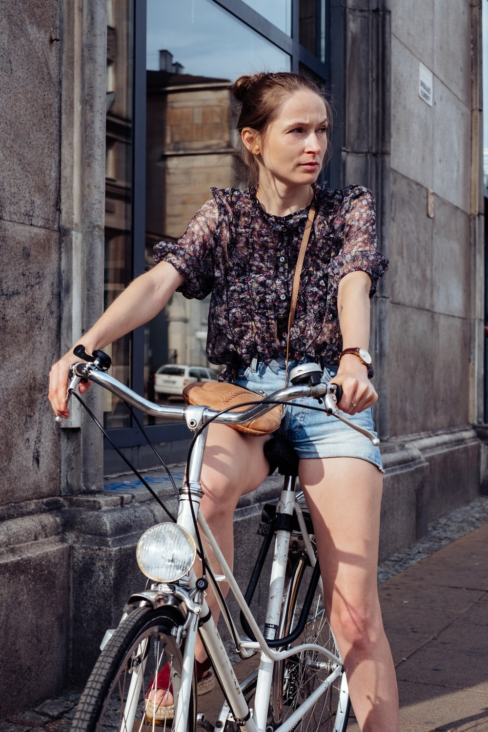woman in black and white floral shirt and blue denim shorts riding on bicycle