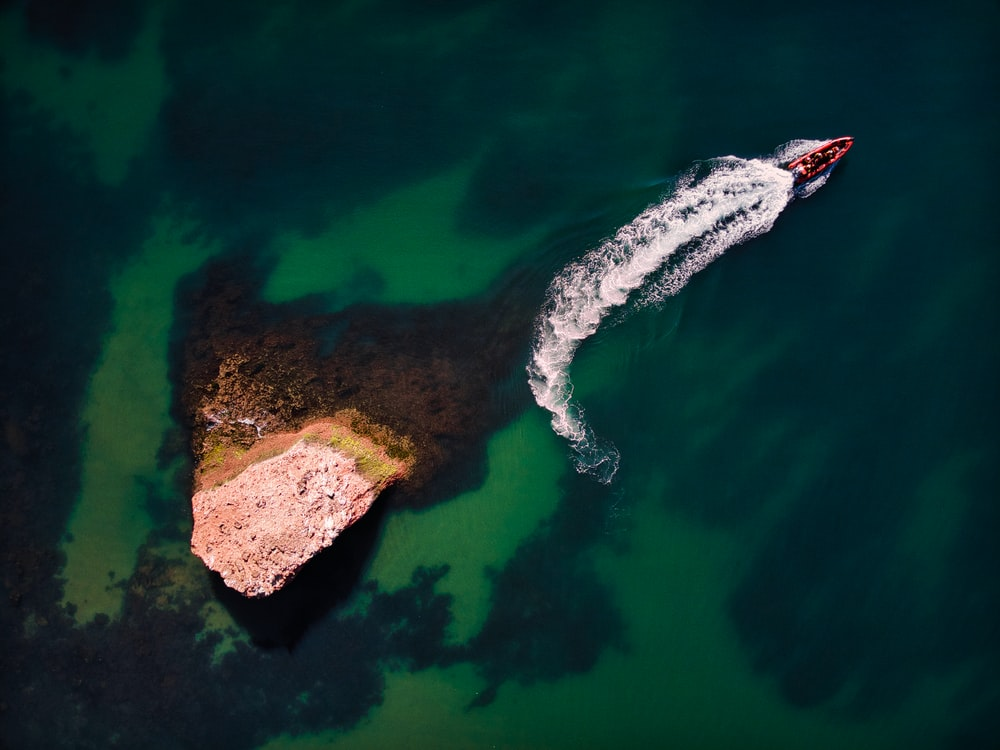 aerial view of brown rock formation on body of water during daytime