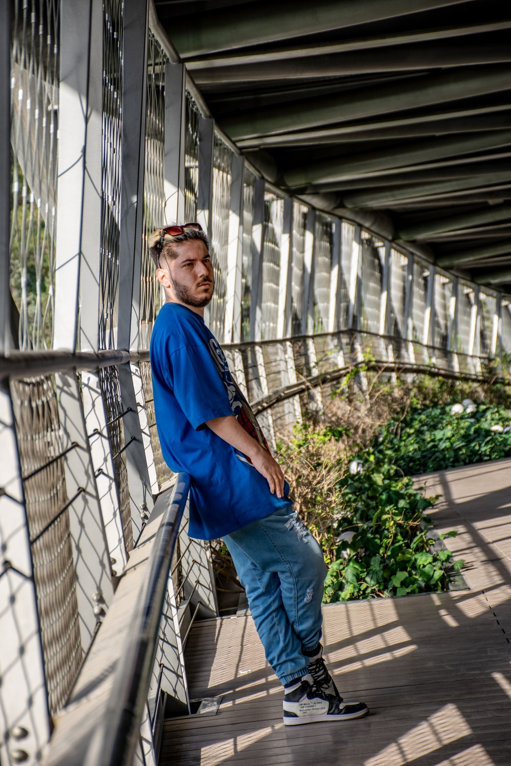 man in blue long sleeve shirt and blue denim jeans standing on gray concrete stairs