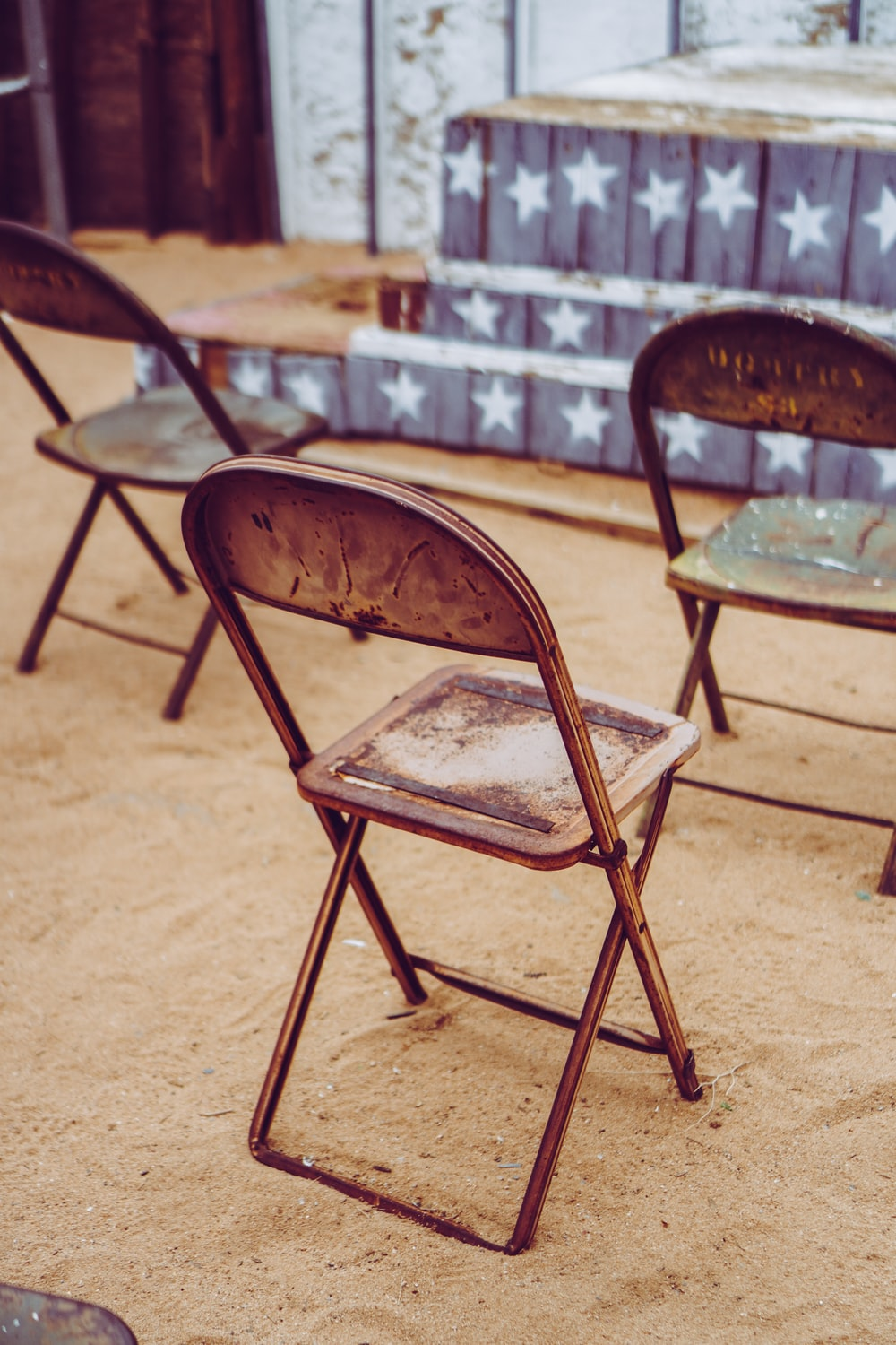brown wooden folding chair on brown sand during daytime