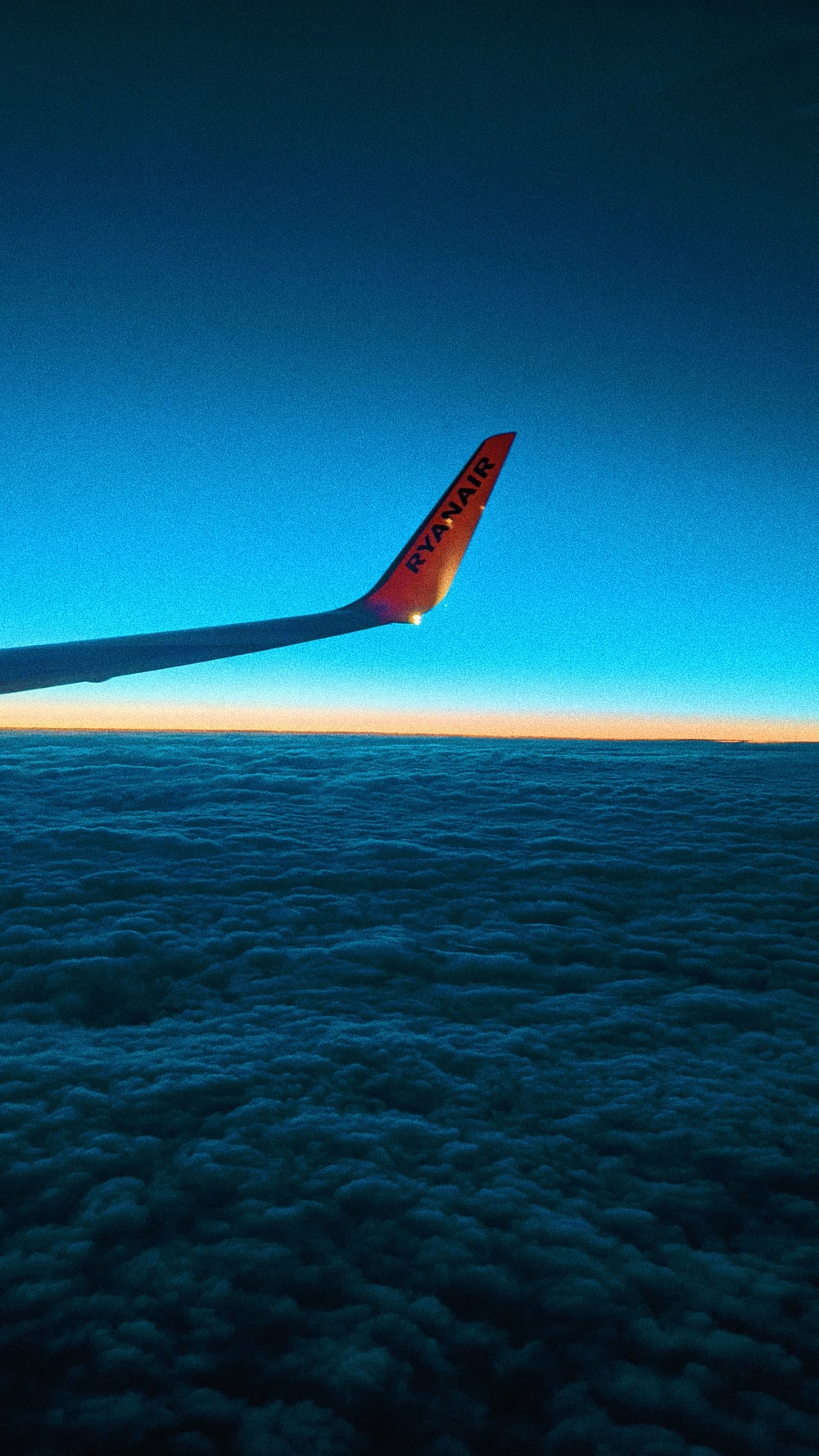 airplane wing over the sea during daytime