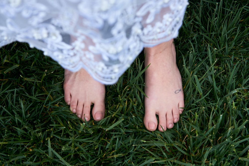person in white lace skirt on green grass field