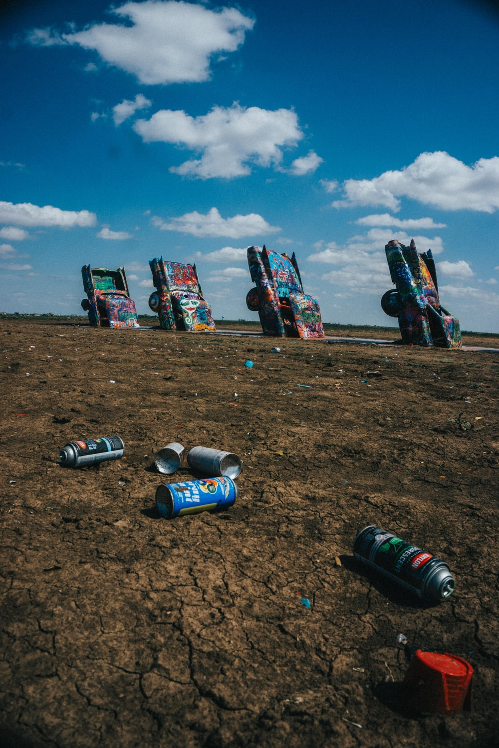 assorted cans on brown sand under blue sky during daytime