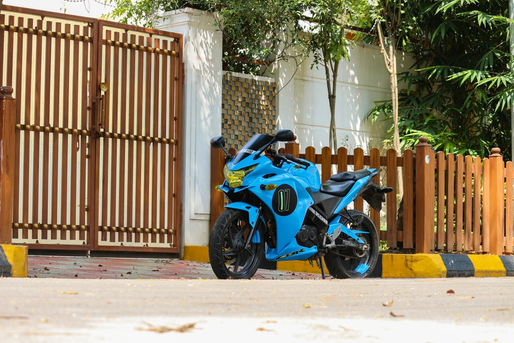 blue sports bike parked beside brown wooden gate during daytime