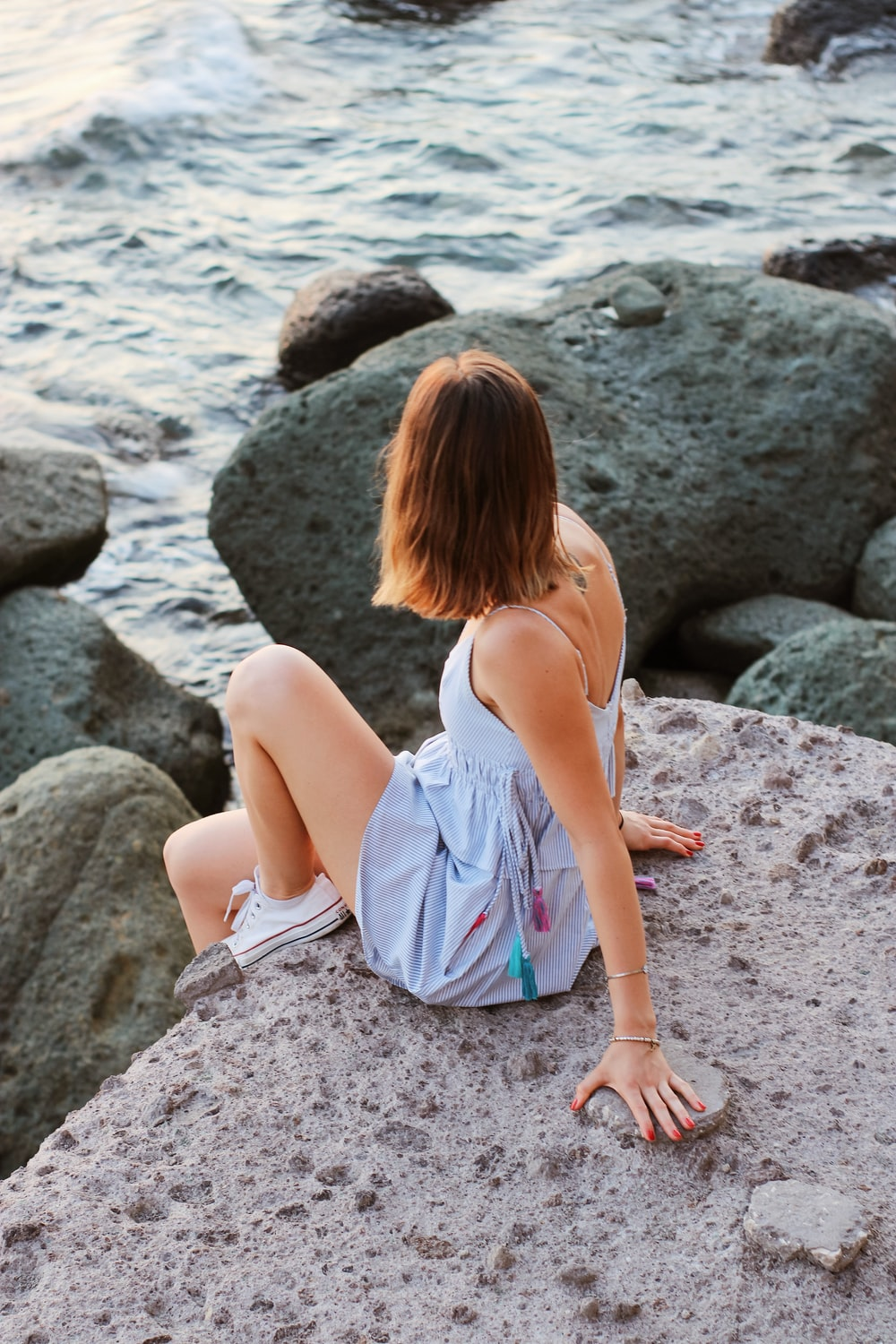 woman in white sleeveless dress sitting on rocky shore during daytime