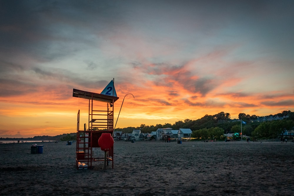 red wooden lifeguard tower on beach during sunset