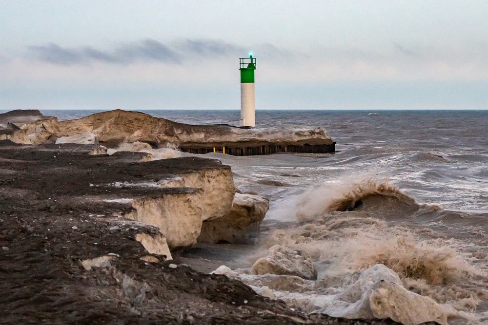 white and green lighthouse on brown rock formation near body of water during daytime