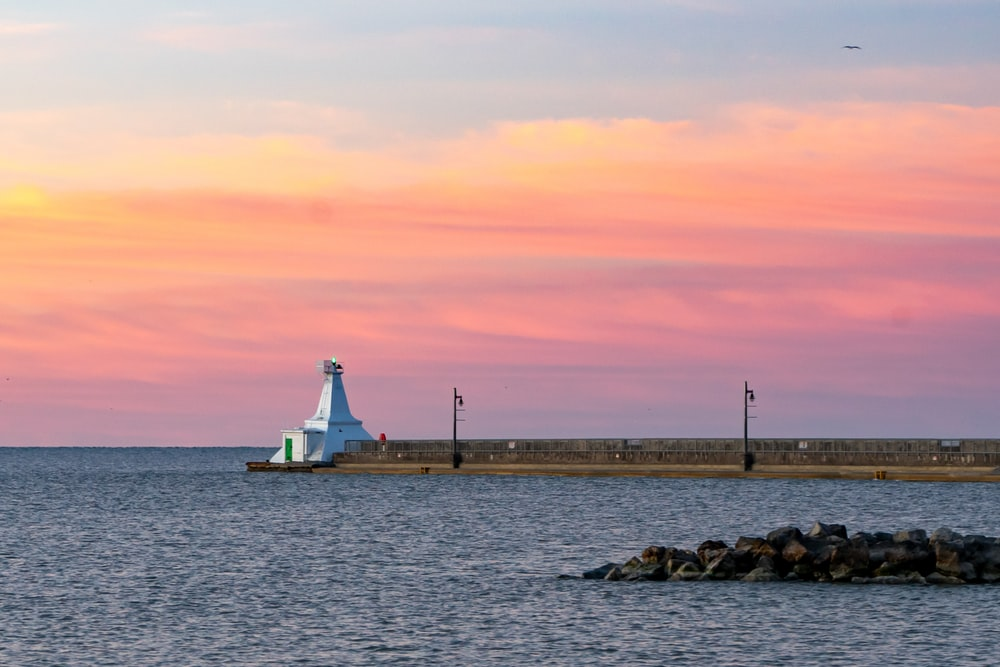 white lighthouse near body of water during sunset