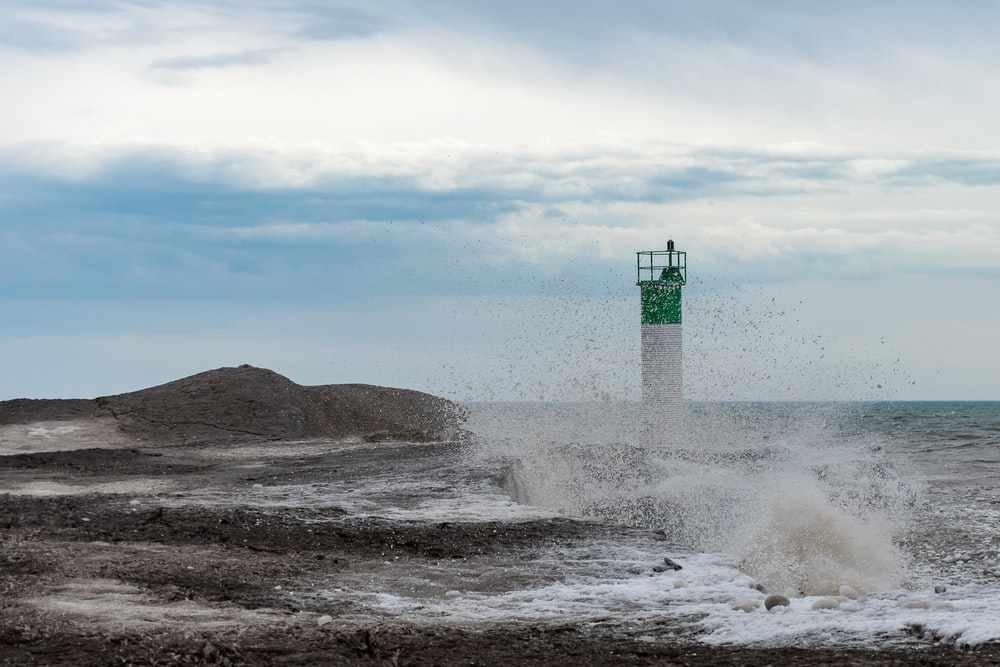 white and green lighthouse on brown rock formation near sea waves during daytime
