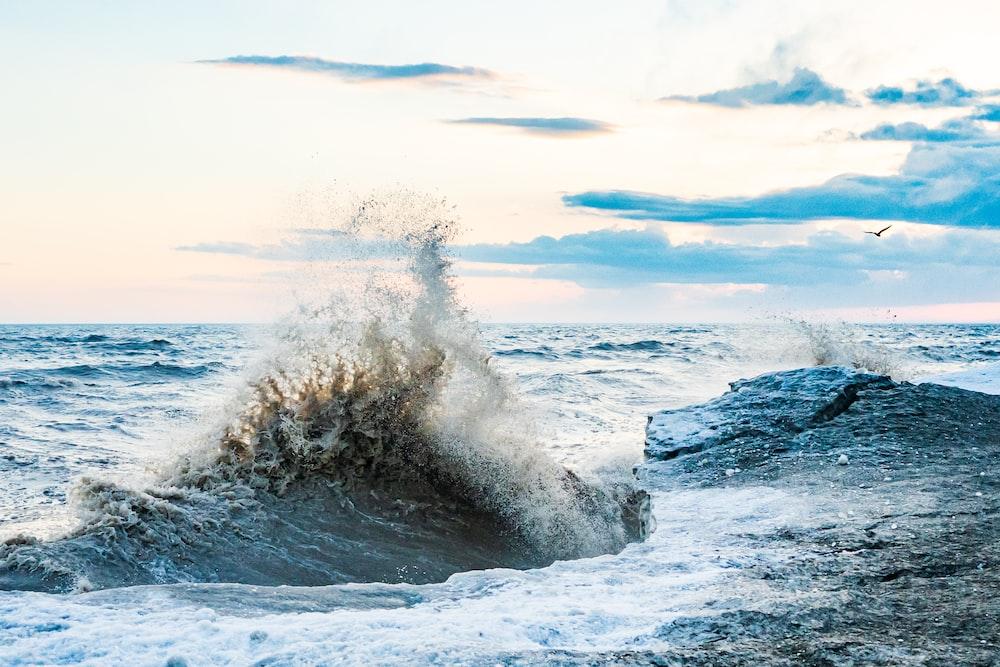 ocean waves crashing on rocks during daytime