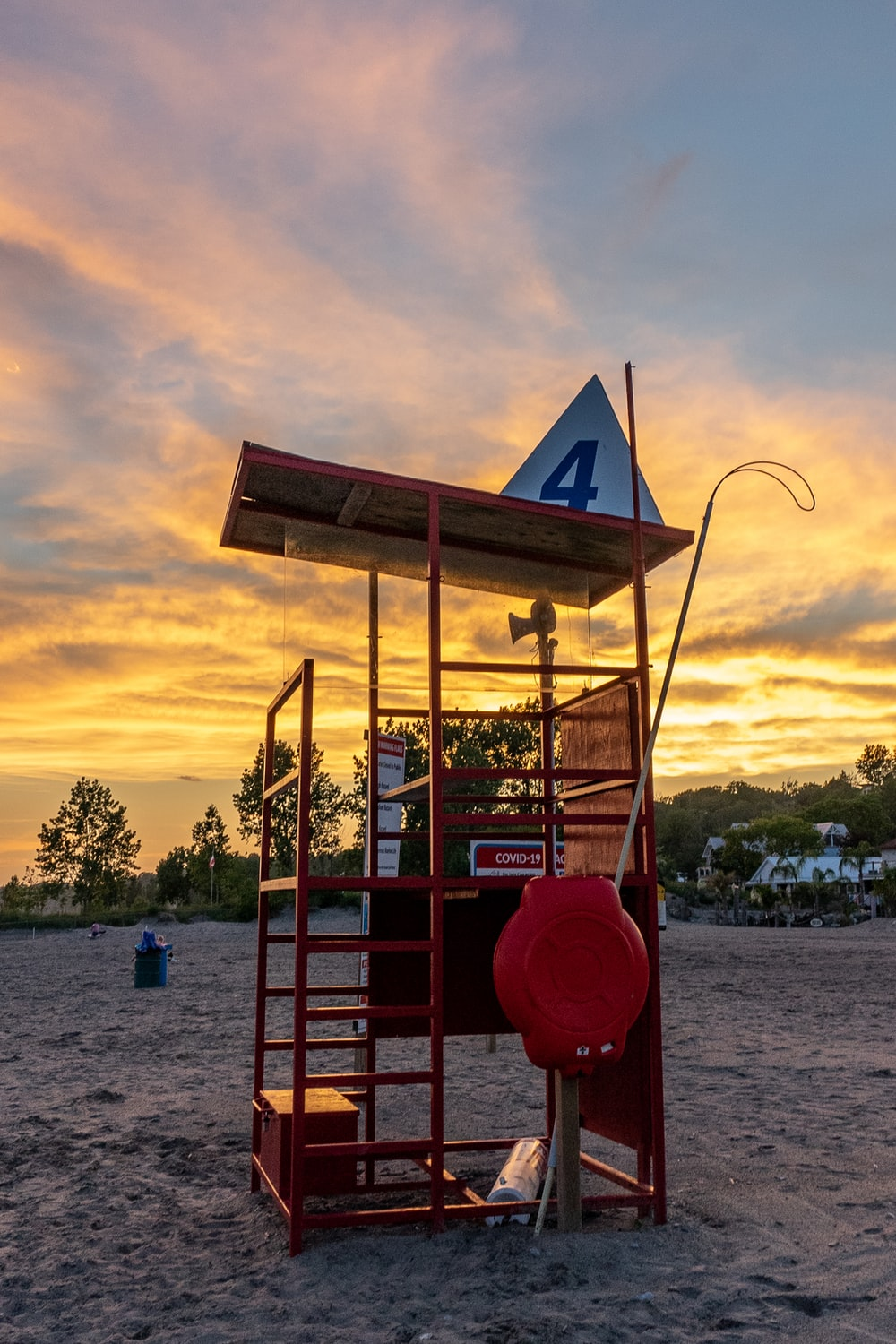 red and brown wooden lifeguard tower near body of water during sunset