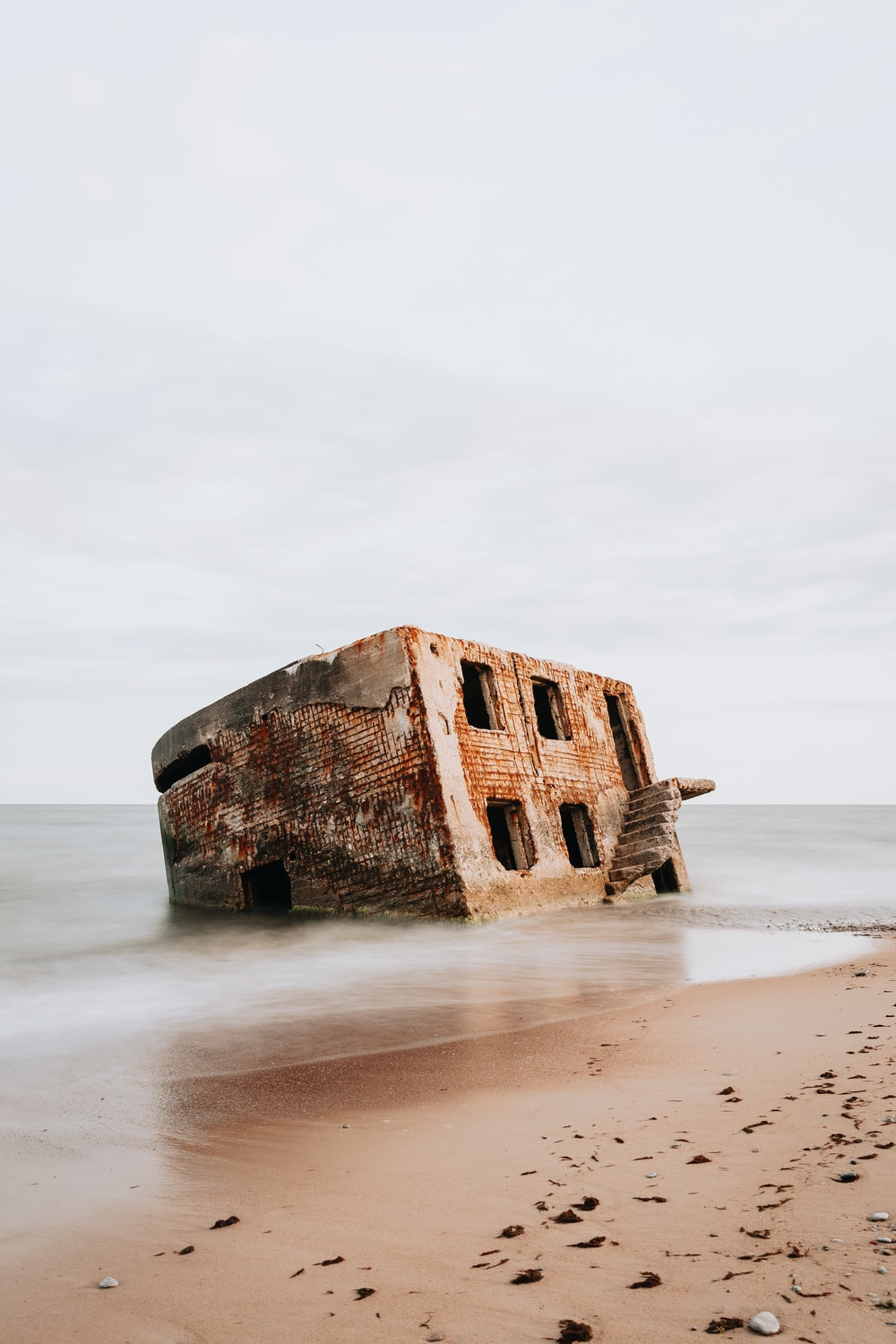 brown concrete building on white sand beach during daytime