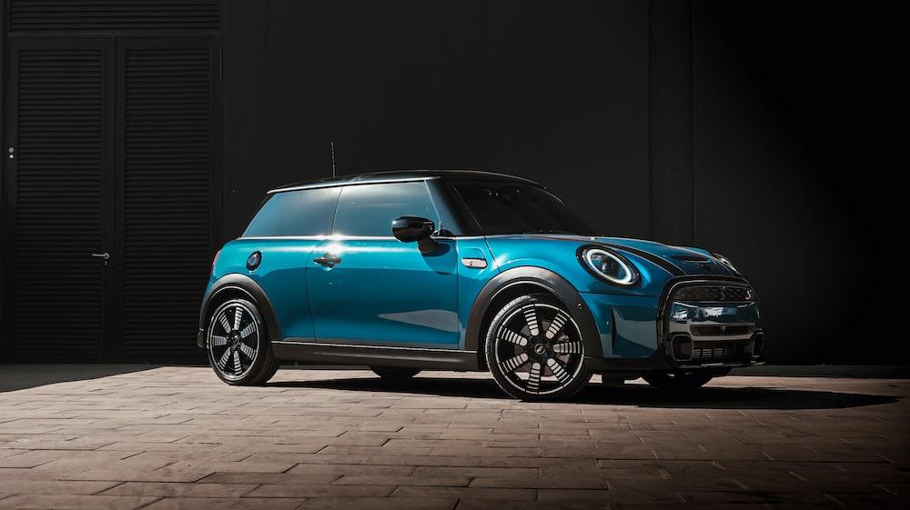 blue volkswagen beetle parked on black background